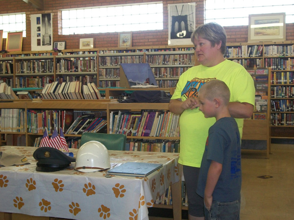 summer reading heroes program - mom and child look at display of helmets and hats