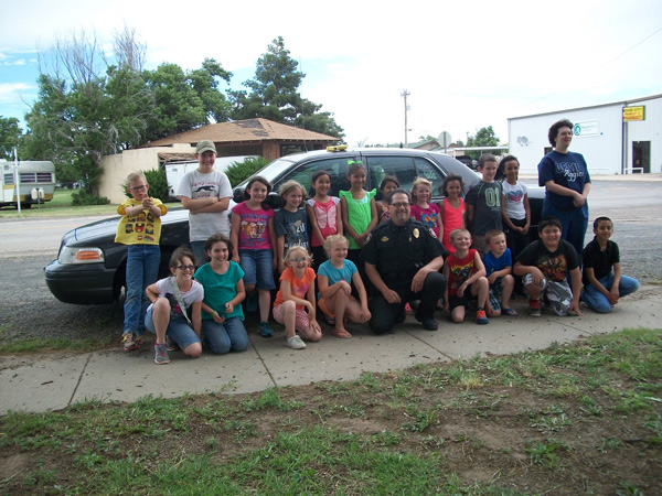 summer reading big group of kids and police officer in front of squad car