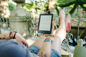 a girl reading an ebook relaxing on a patio